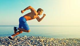 Bemannen Sie den Athleten, der draußen durch Meer bei Sonnenuntergang läuft Stockbilder