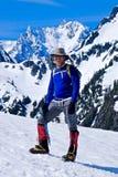 Bemannen Sie den Bergsteiger, der auf die Gebirgsoberseite steht und lächelt Lizenzfreie Stockfotos