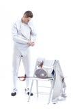 Bemannen Sie den Berufsfechter, der auf schützendes Kostüm auf Weiß sich setzt Lizenzfreie Stockbilder