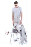 Bemannen Sie den Berufsfechter, der betrachtet, einzäunend Ausrüstung auf Stuhl Stockfoto
