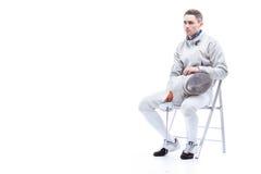 Bemannen Sie den Berufsfechter, der Klinge und Maske beim Sitzen auf Stuhl hält Stockfoto