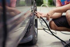 Bemannen Sie den Fahrer, der Luftdruck überprüft und Luft in den Reifen von füllt Stockbilder