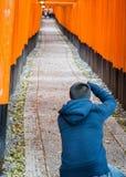 Bemannen Sie den Fotografen, der Fotos in fushimi Inari-Schrein macht Stockbilder