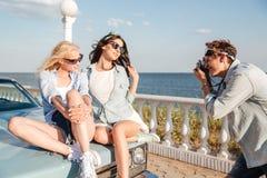 Bemannen Sie den Fotografen, der Fotos von zwei Frauen macht, die auf Auto sitzen Lizenzfreie Stockfotos