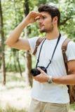 Bemannen Sie den Fotografen, der Kamera hält und weit weg im Wald schaut Lizenzfreies Stockbild