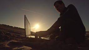 Bemannen Sie den Geschäftsmannfreiberuflerlaptop, der hinter dem Sitzen auf freiberuflich tätig seiendem Schattenbild des Strande stockfotografie