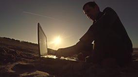 Bemannen Sie den Geschäftsmannfreiberuflerlaptop, der hinter dem Sitzen auf freiberuflich tätig seiendem Schattenbild des Strande stockfotos