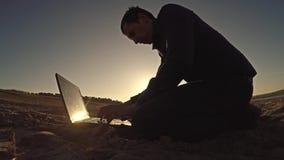 Bemannen Sie den Geschäftsmannlaptopfreiberufler, der hinter dem Sitzen auf freiberuflich tätig seiendem Schattenbild des Strande stockbilder