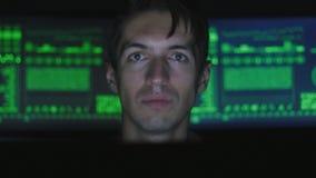 Bemannen Sie den Hackerprogrammierer, der am Computer arbeitet, während grüne Codezeichen über sein Gesicht in der Internetsicher stock footage