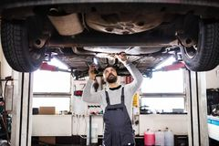 Bemannen Sie den Mechaniker, der ein Auto in einer Garage repariert Lizenzfreies Stockbild