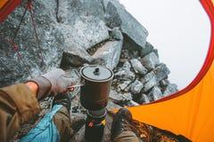 Bemannen Sie den Reisenden, der Lebensmittel im Topf auf Ofenbrenner im Campingzelt kocht lizenzfreies stockfoto