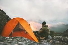 Bemannen Sie den Reisenden, der sich nahe in den Bergen des Zeltkampierens entspannt stockfotos