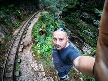 Bemannen Sie den Reisenden und Wanderer, die selfie durch eine Hand in der Gebirgsschlucht mit alter Eisenbahn nehmen Stockfotografie