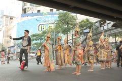 Bemannen Sie den Reitenunicycle, der selfie mit Gruppe thailändischen traditionellen Tänzern nimmt Stockbild