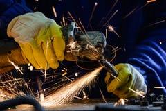 Bemannen Sie den Schnitt des Stahlrohres mit einem Winkelschleifer, heiße Funken produzierend Lizenzfreie Stockbilder
