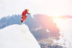 Bemannen Sie den Snowboarder, der von der Spitze des schneebedeckten Hügels mit Snowboard am Abend bei Sonnenuntergang springt Lizenzfreies Stockbild