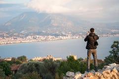 Bemannen Sie den Touristen, der Fotos einer Stadt vom Höhepunkt macht Stockbilder