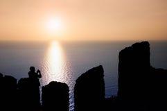 Bemannen Sie den Touristen, der Fotos eines Sonnenuntergangs im Meer macht Stockfoto
