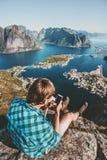 Bemannen Sie den Touristen, der den Smartphone verwendet, der auf Klippenrand sich entspannt Stockbild