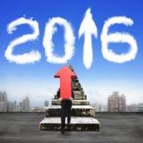 Bemannen Sie den tragenden Pfeil, der oben alte Treppe in Richtung zu 2016 Wolken klettert Lizenzfreie Stockbilder