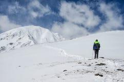 Bemannen Sie den tragenden Sturzhelm, der weg schaut und in der Schneegebirgshügellandschaft denkt Lizenzfreies Stockbild