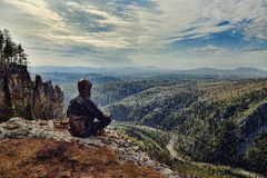 Bemannen Sie den Wanderer, der auf Berg am regnerischen Tag sitzt, es ist nasses schlechtes Wetter stockbilder