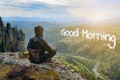 Bemannen Sie den Wanderer, der auf Gebirgssitzungssonnenaufgang, Beschriftung des guten Morgens in der Form von Wolken sitzt lizenzfreie stockbilder