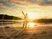 Bemannen Sie den Wandererwanderer, der mit Rucksack auf Seeufer am sonnigen Abend geht Abenteuer, Tourismus Activelebensstil Stockfotografie