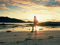 Bemannen Sie den Wandererwanderer, der mit Rucksack auf Seeufer am sonnigen Abend geht Abenteuer, Tourismus Activelebensstil Stockfoto