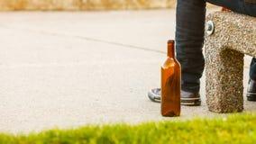 Bemannen Sie deprimiertes mit der Weinflasche, die auf Bank der im Freiensitzt Stockbilder