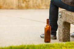 Bemannen Sie deprimiertes mit der Weinflasche, die auf Bank der im Freiensitzt Stockfoto
