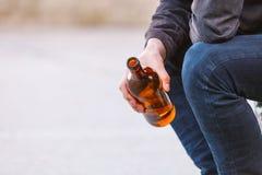 Bemannen Sie deprimiertes mit der Weinflasche, die auf Bank der im Freiensitzt Stockbild