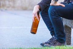 Bemannen Sie deprimiertes mit der Weinflasche, die auf Bank der im Freiensitzt Lizenzfreie Stockbilder