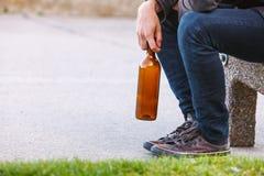 Bemannen Sie deprimiertes mit der Weinflasche, die auf Bank der im Freiensitzt Lizenzfreies Stockbild