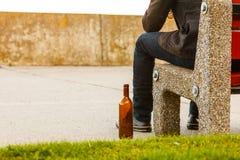 Bemannen Sie deprimiertes mit der Weinflasche, die auf Bank der im Freiensitzt Stockfotos