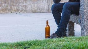 Bemannen Sie deprimiertes mit der Weinflasche, die auf Bank der im Freiensitzt Stockfotografie