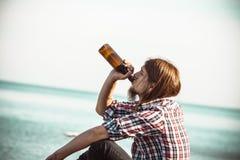 Bemannen Sie deprimiertes mit der Weinflasche, die auf Strand dem im Freiensitzt Stockbilder