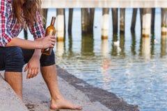 Bemannen Sie deprimiertes mit der Weinflasche, die auf Strand dem im Freiensitzt Lizenzfreies Stockfoto