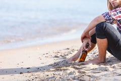Bemannen Sie deprimiertes mit der Weinflasche, die auf Strand dem im Freiensitzt Stockbild