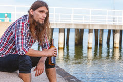 Bemannen Sie deprimiertes mit der Weinflasche, die auf Strand dem im Freiensitzt Lizenzfreie Stockfotografie
