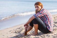Bemannen Sie deprimiertes mit der Weinflasche, die auf Strand dem im Freiensitzt Lizenzfreies Stockbild