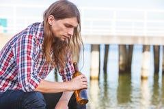 Bemannen Sie deprimiertes mit der Weinflasche, die auf Strand dem im Freiensitzt Lizenzfreie Stockfotos