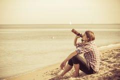 Bemannen Sie deprimiertes mit der Weinflasche, die auf Strand dem im Freiensitzt Lizenzfreie Stockbilder