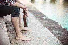 Bemannen Sie deprimiertes mit der Weinflasche, die auf Strand dem im Freiensitzt Stockfoto