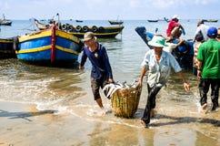 Bemannen Sie die Arbeitskräfte, die den tiefen Bambuskorb tragen, der mit Fischen am langen Hai-Fischmarkt, Ba-Ria Vung Tau-Provi Stockbild