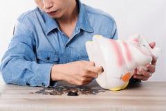 Bemannen Sie die Auswahl des Geldes von Sparschwein oder die Rettung des Behälters auf Schreibtisch Lizenzfreie Stockfotografie
