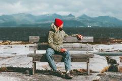 Bemannen Sie die Entspannung auf der Bank, die Meer genießt und Berge gestalten Reise-Lebensstilkonzeptskandinavier landschaftlic Stockfotos