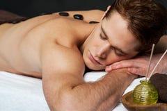 Bemannen Sie die Entspannung auf einem Massagebett mit heißen Steinen Stockfotos