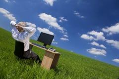 Bemannen Sie die Entspannung am Büro-Schreibtisch auf einem grünen Gebiet Lizenzfreies Stockfoto