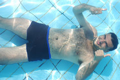 Bemannen Sie die Entspannung an der Unterseite des Swimmingpools lizenzfreies stockbild